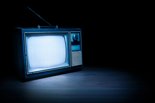 High contrast image of an old vintage TV with white noise on white wood-img-blog